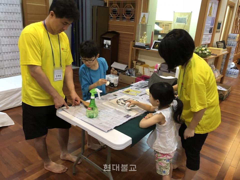 선운사 전통산사문화재 활용프로그램에 참가한 가족들이 탁본체험을 하고 있다.