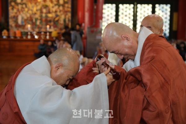 조계종 총무원장 원행 스님(왼쪽)이 대종사법계를 품수한 일면 스님에게 불자를 봉정하고 있다.