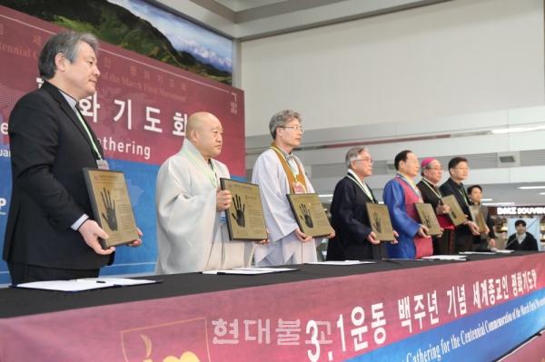 국내 7대 종교지도자들이 세계평화를 염원하는 기도문에 서명하고, 각자의 핸드프린팅을 남긴 동판을 들고 기념촬영하는 모습