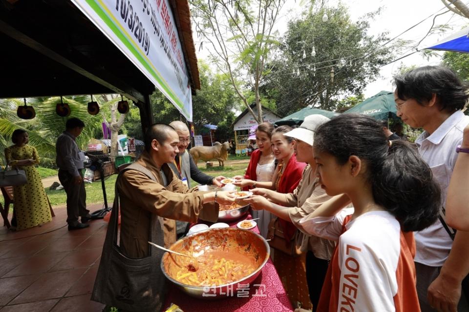 태고종 전북종무원장 진성스님과 베트남 스님이 닥락성 커피축제에서 떡볶이를 참가자들에게 나눠주고 있다.
