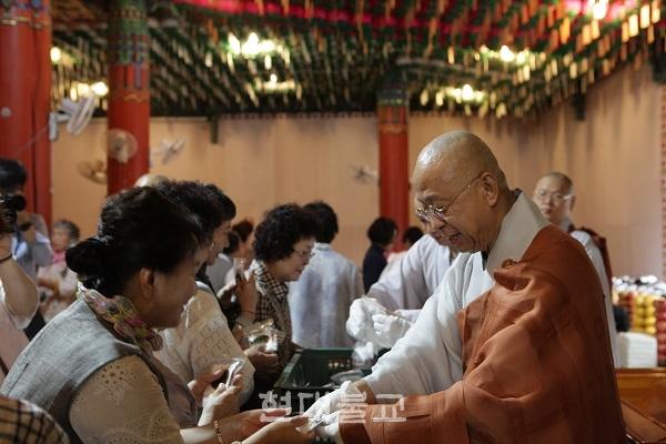 단오절을 맞아 통도사 주지 현문 스님이 신도들에게 소금을 나눠주고 있다. 통도사는 6월 7일 설법전에서 용왕재를 봉행하고 화마가 없기를 기원했다.