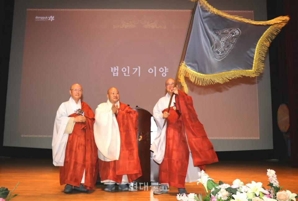 학교법인 동국대학교는 7월 18일 학내 본관 중강당에서 열린 39·40대 이사장 이취임식에서 신임이사장 법산 스님이 법인기를 이양받고 들어보이고 있다.
