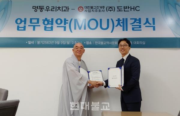 (주)도반HC 사장 주혜 스님과 정명진 명동우리치과 대표원장이 양해각서에 서명 후 기념촬영하고 있다.