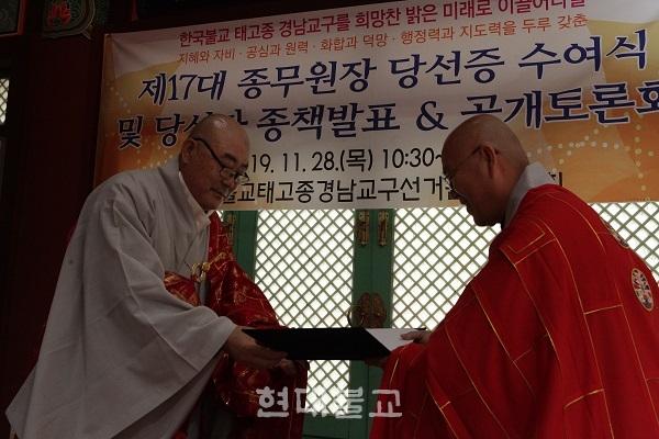 제17대 종무원장 환명 스님(왼쪽)이 당선증을 받고 있다.