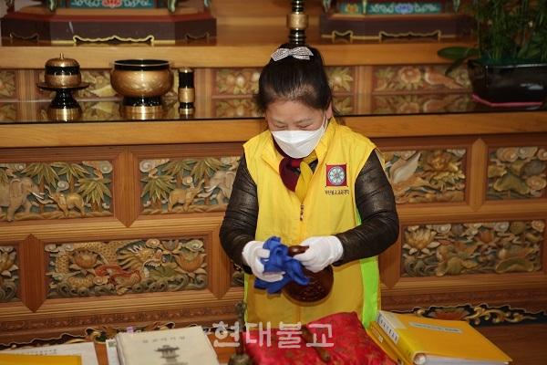부산불교교육대학에서 공부하고 있는 한 불자가 목탁을 소독하고 있는 모습. 이날 방역 봉사에는 학장 범혜 스님을 비롯해 학생들과 봉사자 등 10여명이 동참했다.