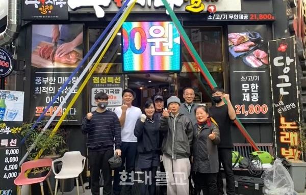 부산불교교육대학 학장 범혜 스님과 봉사자들이 방역 후 상가 앞에서 기념사진을 찍고 있다.