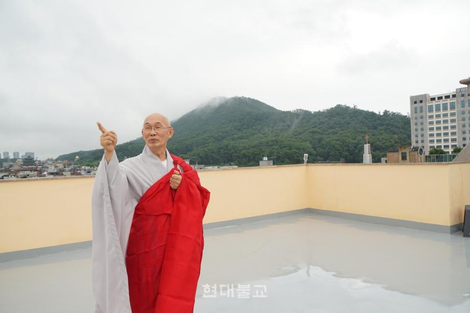 안심정사 회주 법안 스님이 안심빌딩 옥상에 올라 한국불교 미래를 위한 청사진을 설명하고 있다.