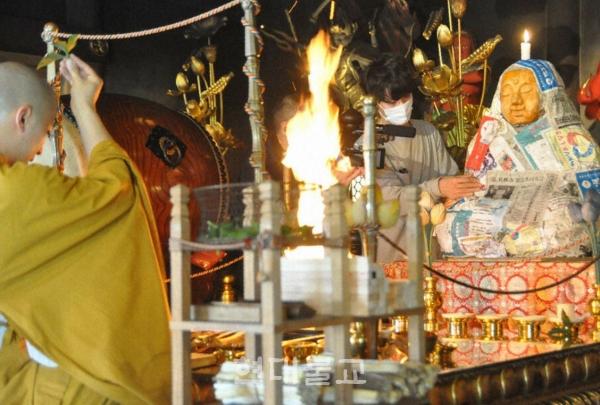 '코로나 대불'을 조성을 위해 마련된 '권진불상'에 코로나로 중지된 이벤트의 전단지를 붙이고 있다. 사진출처=마이니치 신문
